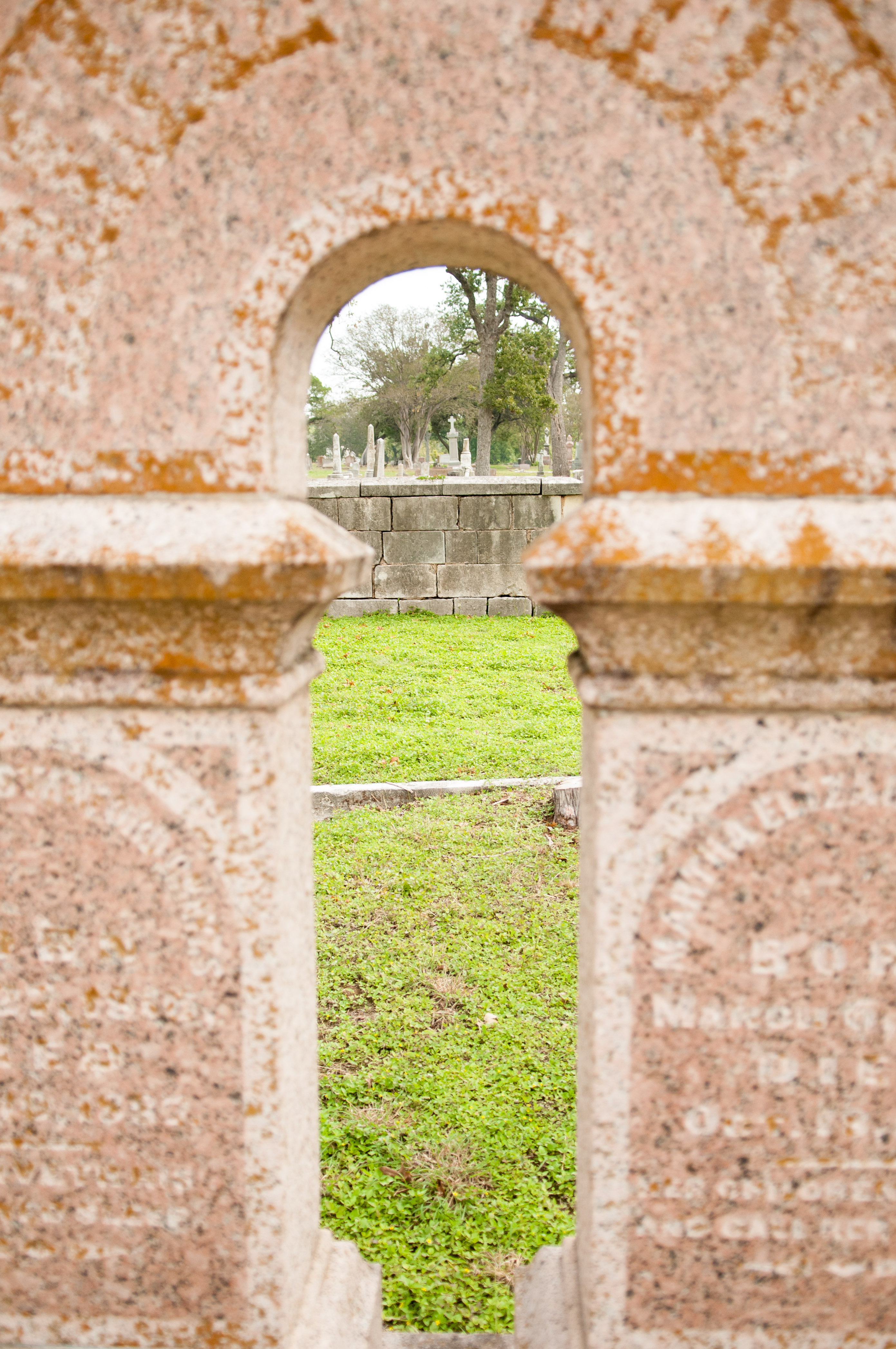 A peek through a headstone into the graveyard at Oakwood Cemetery. Photo by Skylar Isdale