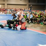 """A skater from both the Rhinestone Cowgirls and the Cherry Bombs fight each other as a result of spinning the """"penalty wheel.""""Photo by Skylar Isdale"""