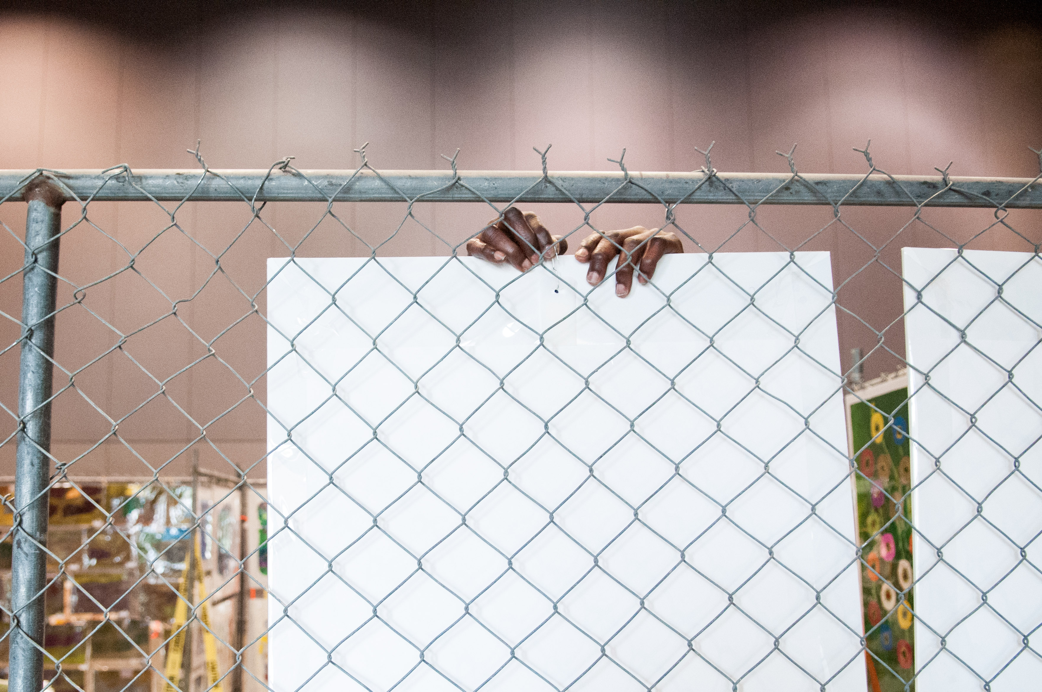 An artist hangs his art pieces at the Austin Convention Center. Photo by Skylar Isdale