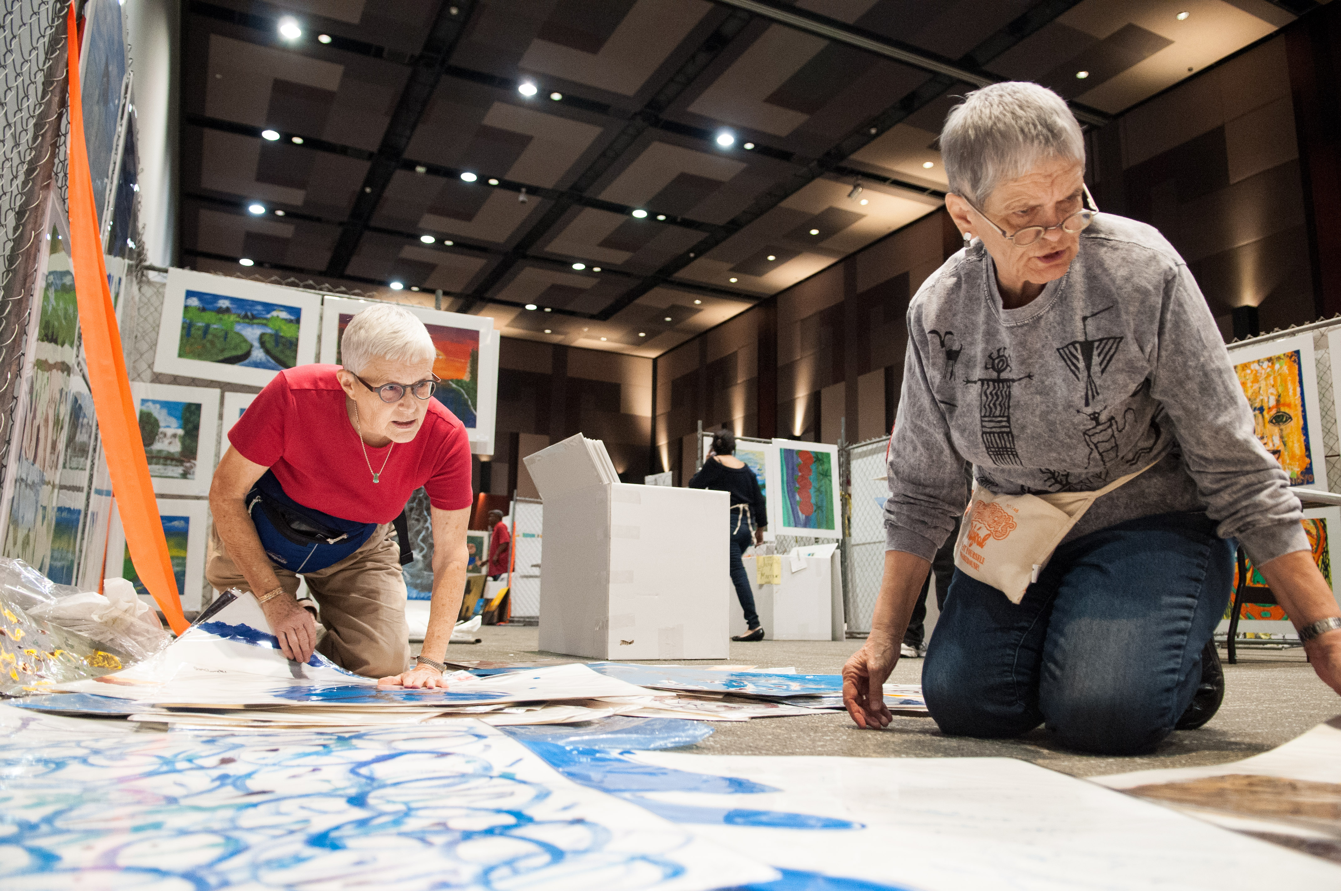 Two volunteers look through art pieces to see which ones will be hung for the show. Photo by Skylar Isdale