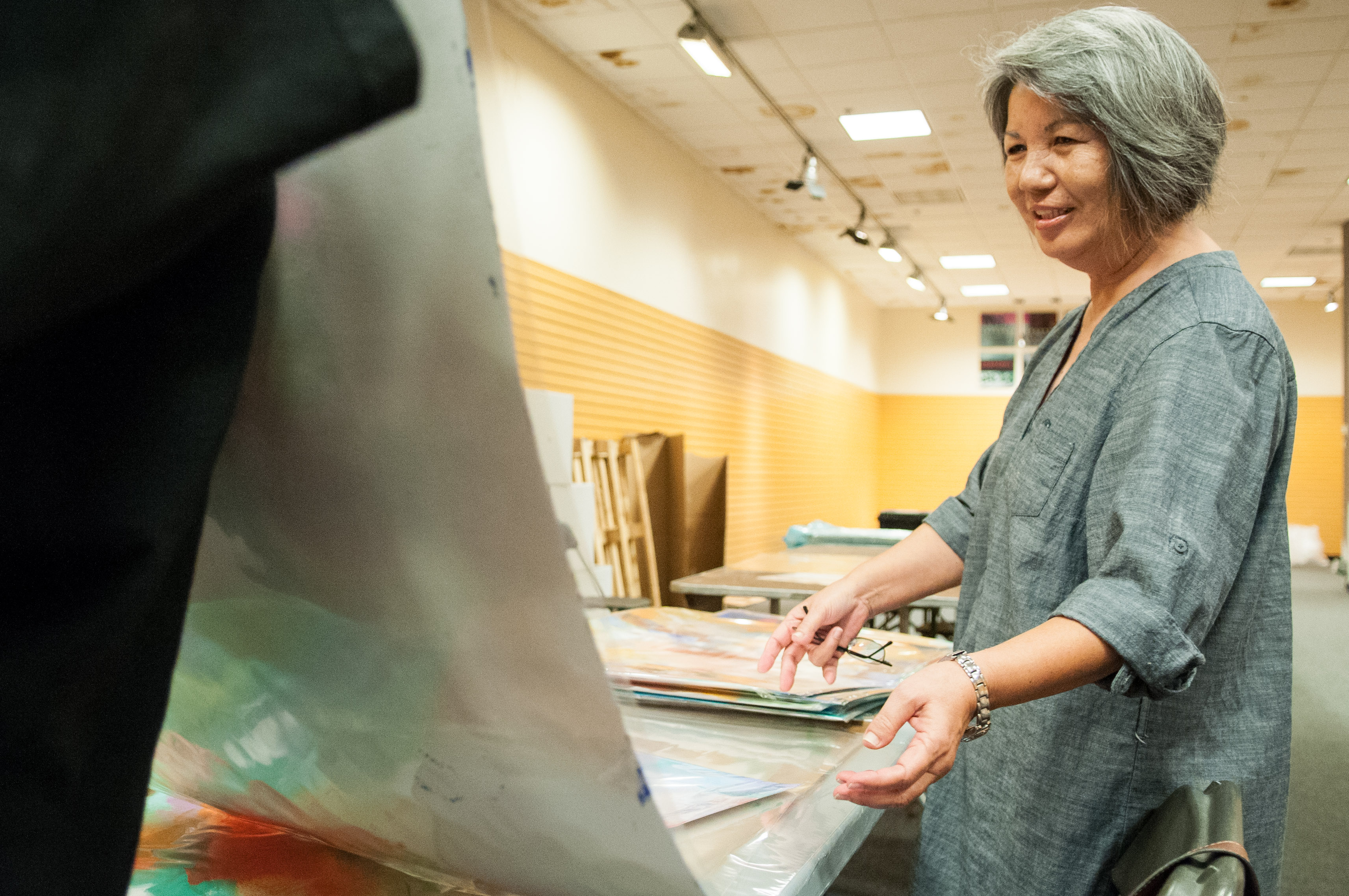 An artist looks at her piece of work to decide which will be mounted for the show. Photo by Skylar Isdale