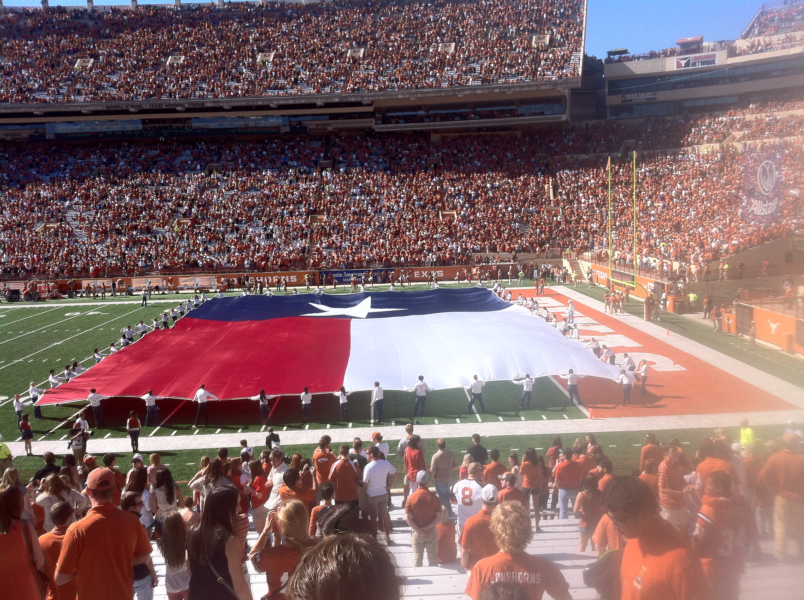 It's a pre-game tradition at Longhorn games to unveil the Texas flag.  Alpha Phi Omega is the group in charge of showing the flag.
