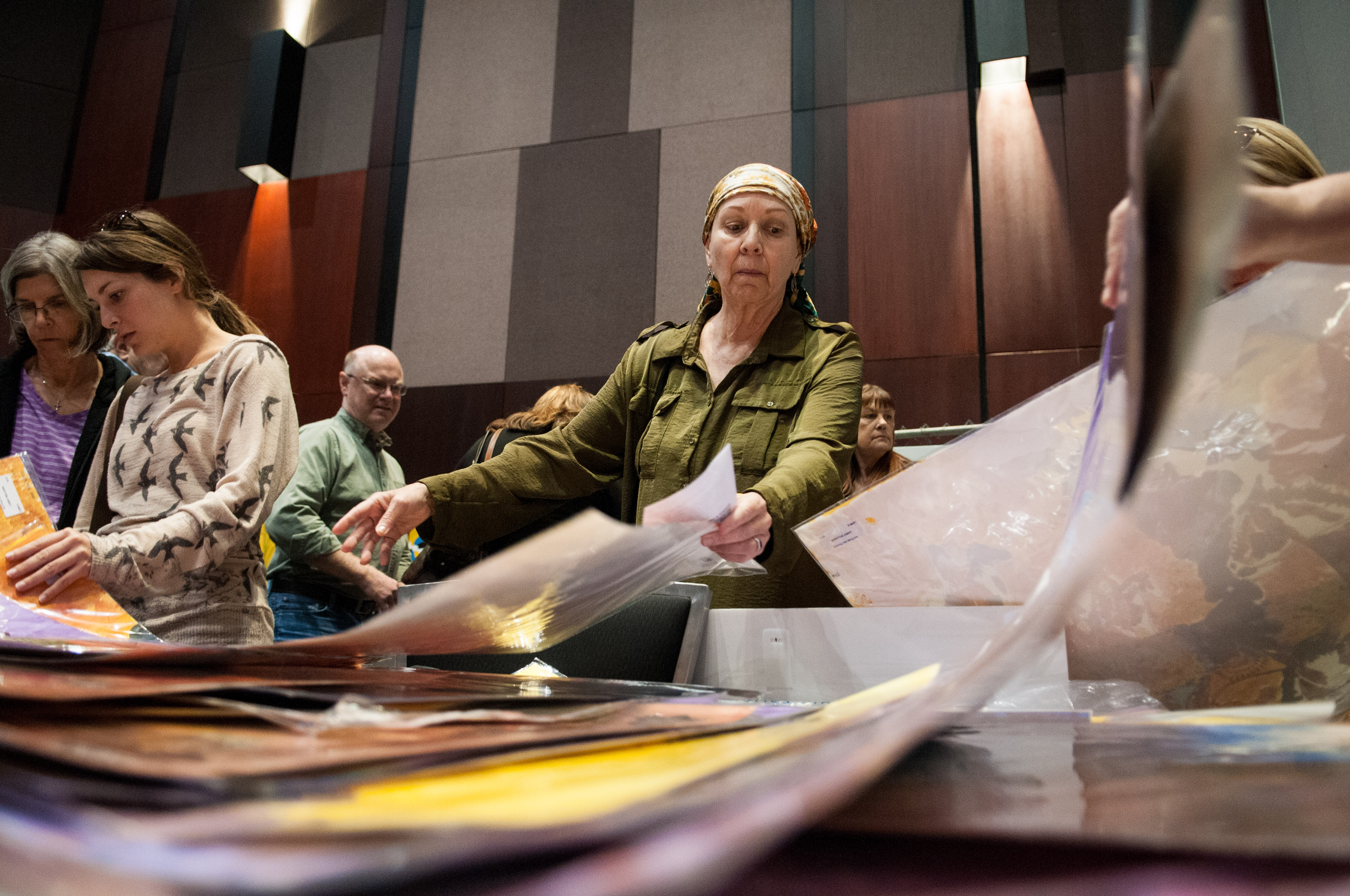People look through art pieces on the table at the Austin Convention Center. People are looking at the various art pieces for sale at the Austin Convention Center. Photo by Skylar Isdale