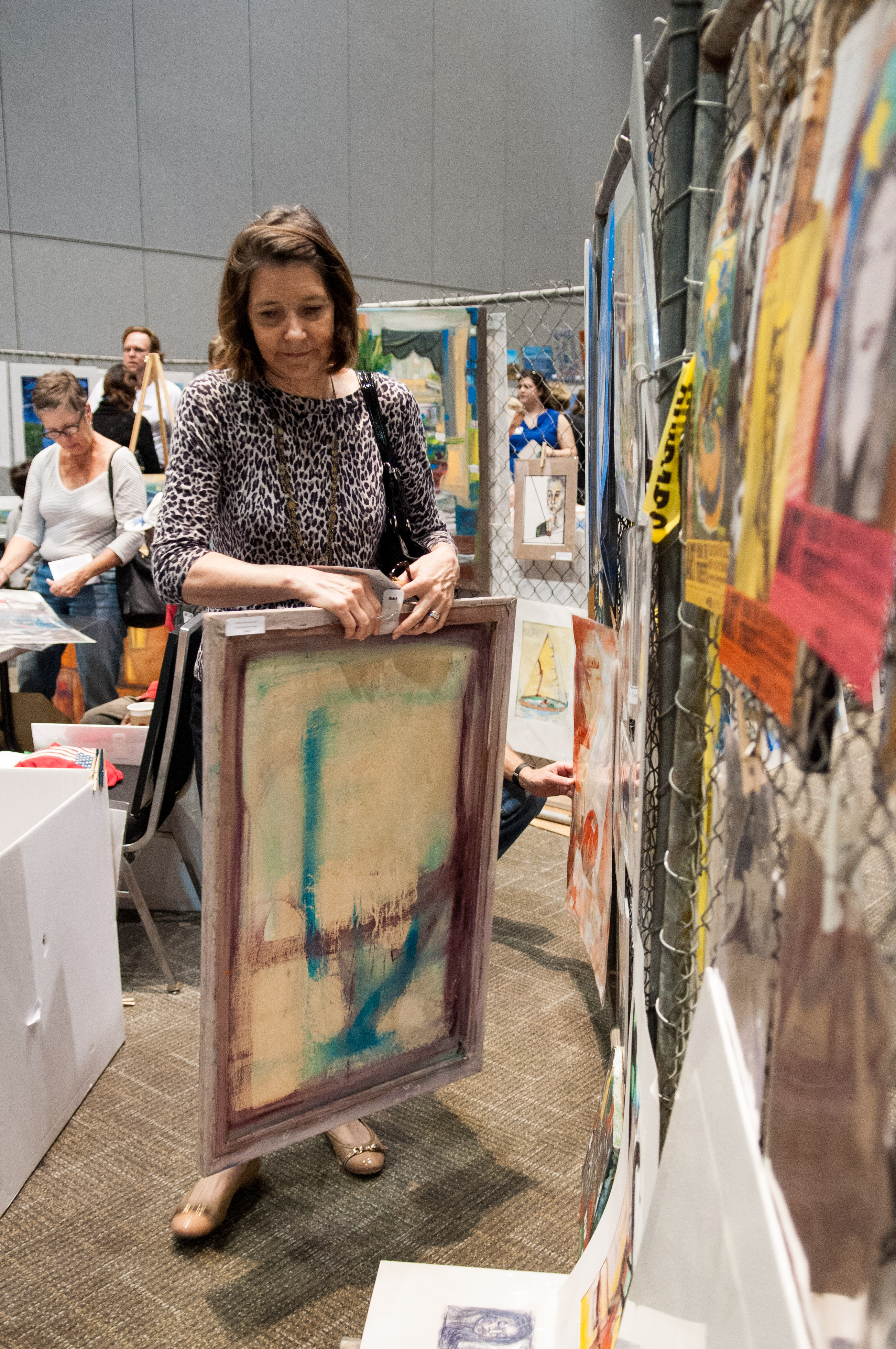 A woman takes down the art piece she is going to buy from the Art from the Streets Show and Sale. Photo by Skylar Isdale