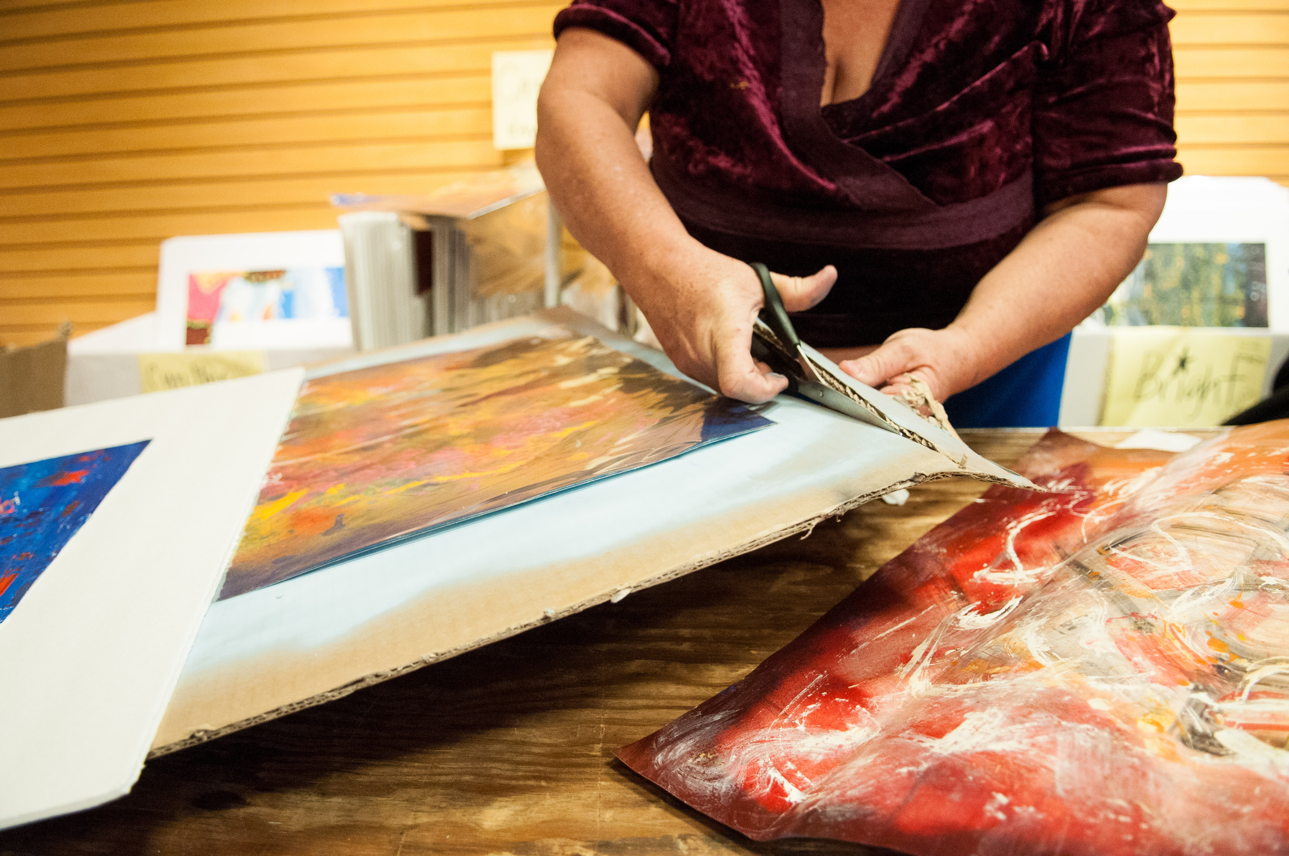 An artist cuts her art piece to the right size for mounting. Photo by Skylar Isdale