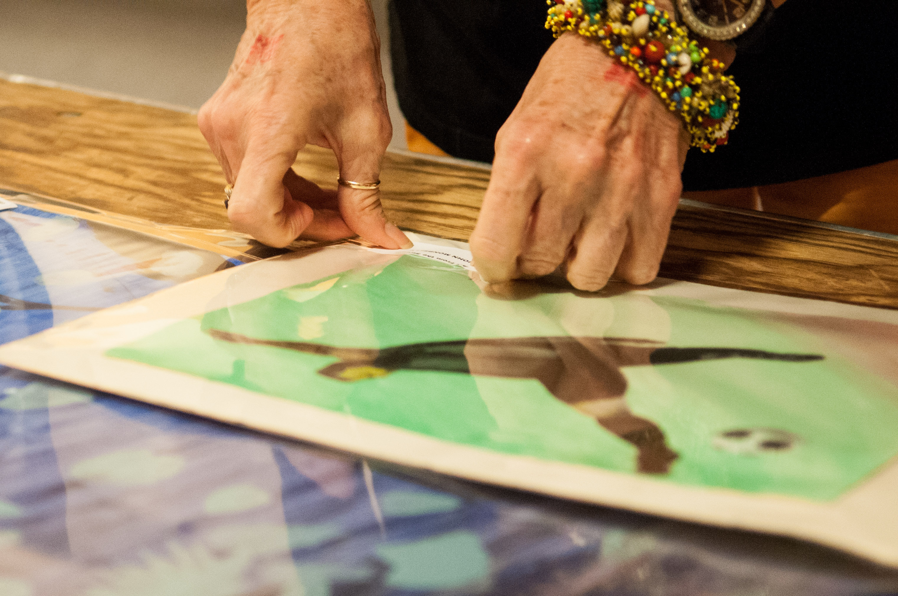 A volunteer labels an art piece with the price for the show. Photo by Skylar Isdale