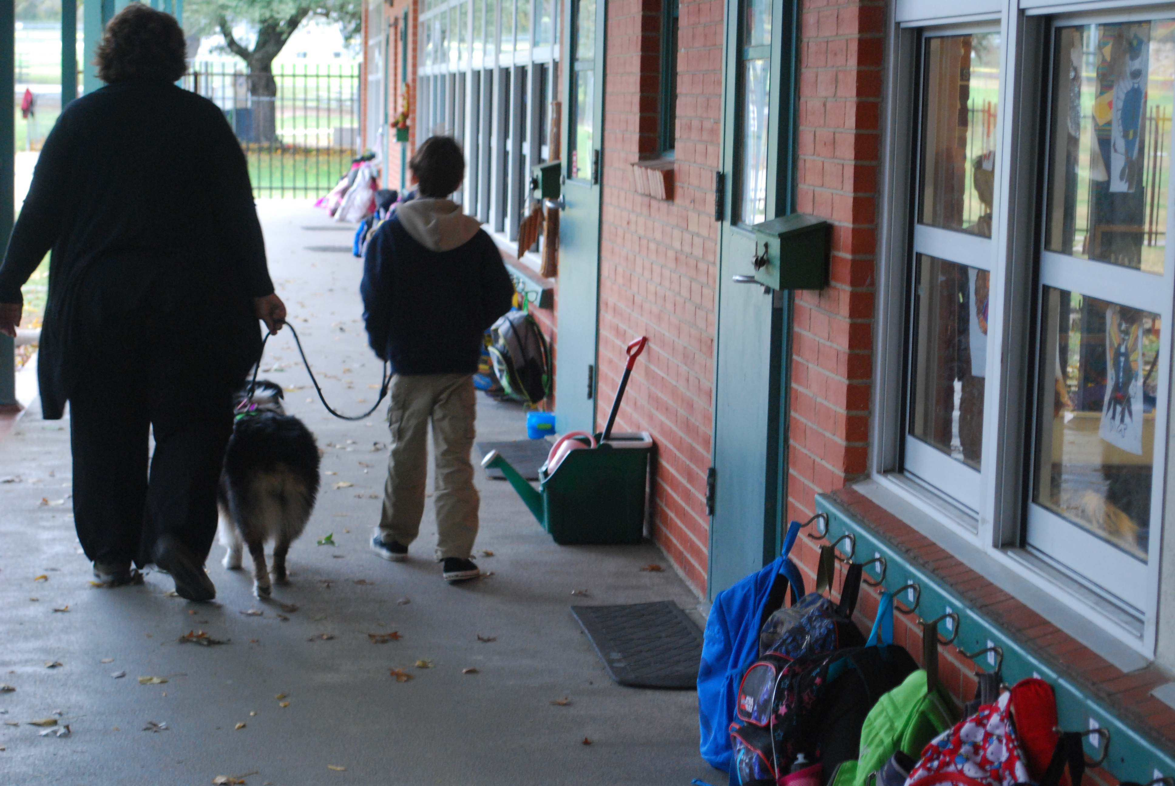 Maddie and volunteer Lee Bowman walk with a Gullett Elementary School student