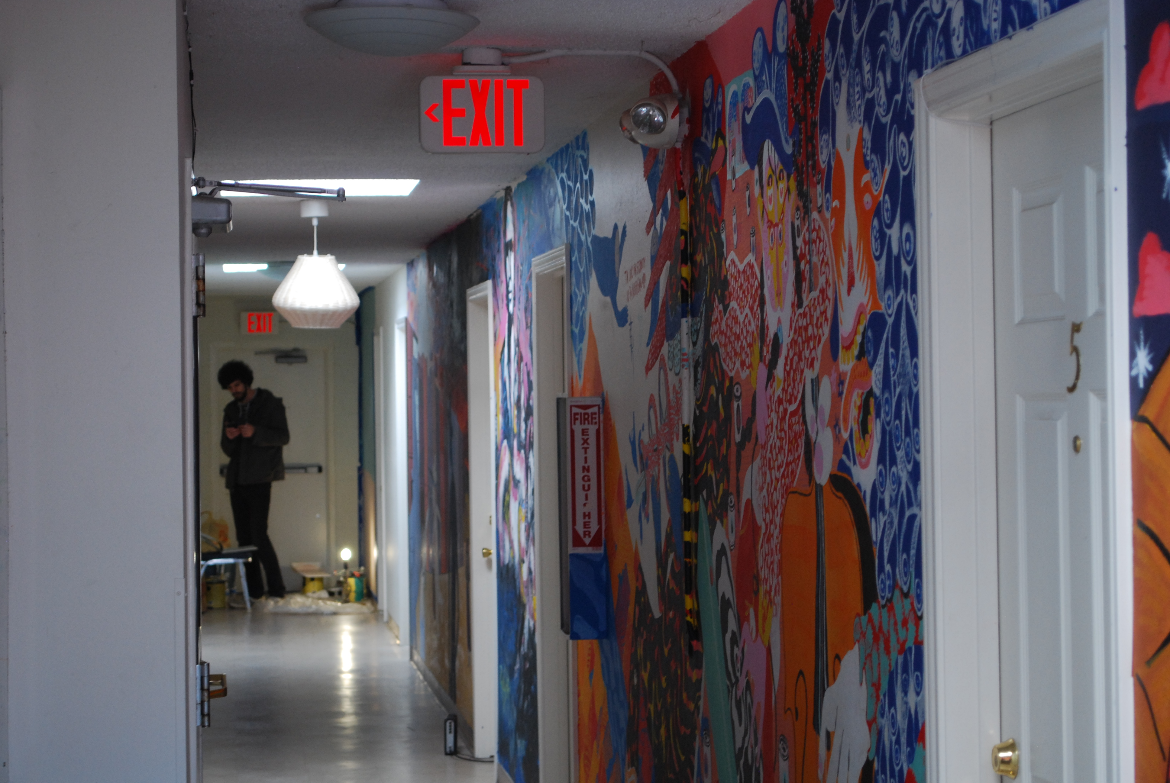 Artist Stephen Ferguson stands at the end of the hall painting a mural of a cowboy riding a giant snake, a design that fits the western theme at Drifter Jack's Hostel. By Kaine Korzekwa