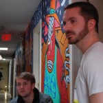 Artist Baylor Estes talks with Drifter Jack's Hostel owner Andy Ward as artist Stephen Ferguson walks toward them from his mural location at the end of the hallway. By Kaine Korzekwa