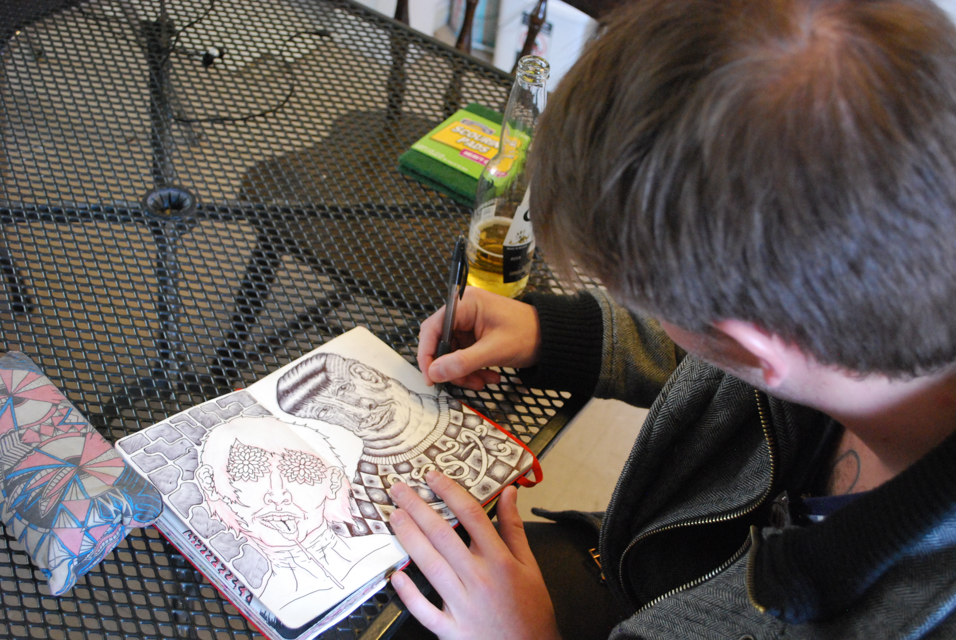 Artist Baylor Estes sits in the dining area of Drifter Jack's Hostel sketching future design ideas. By Kaine Korzekwa