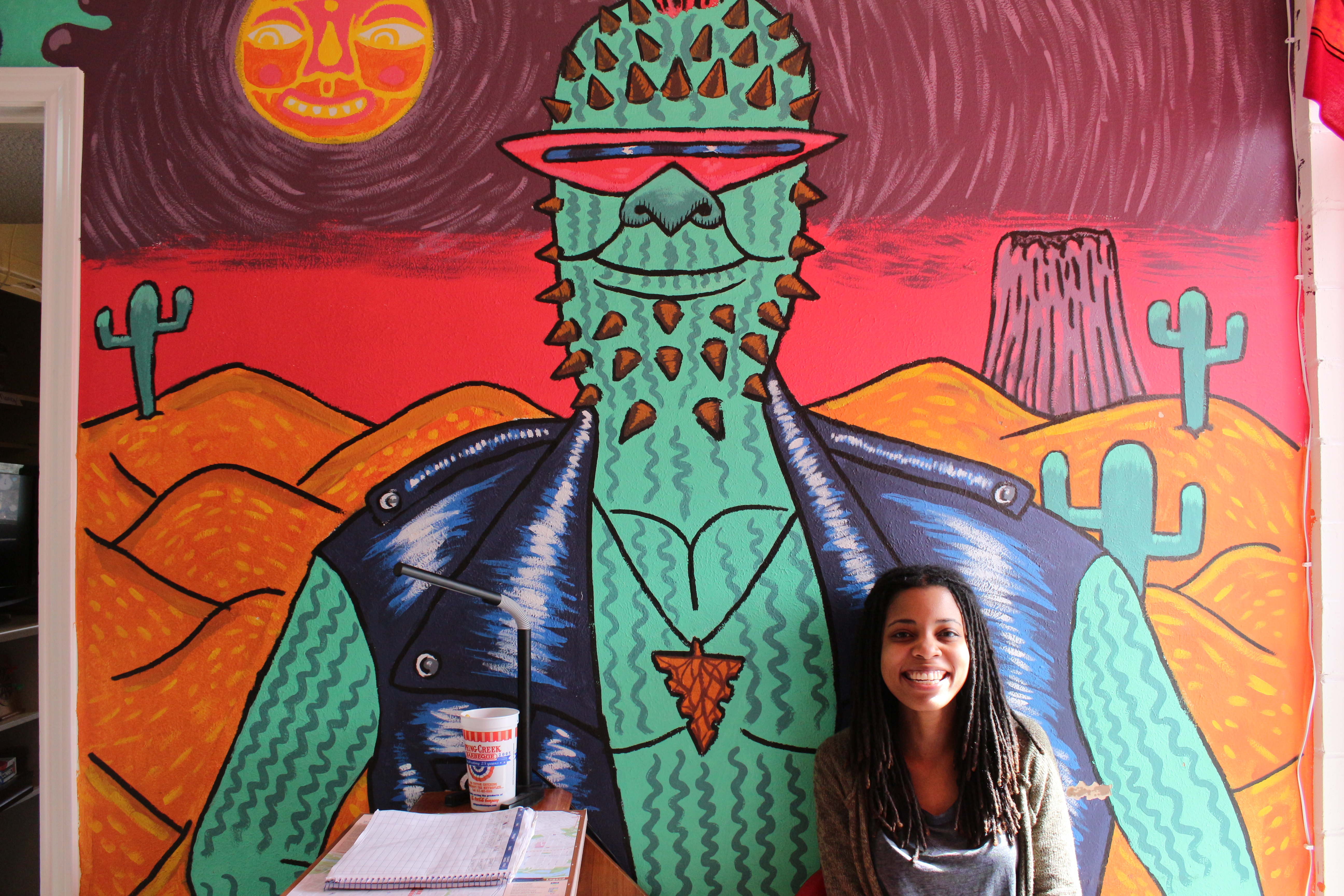 Drifter Jack's Hostel employee Michelle Dotson sits behind the reception desk in front of  a mural painted by Baylor Estes. By Joan Vinson
