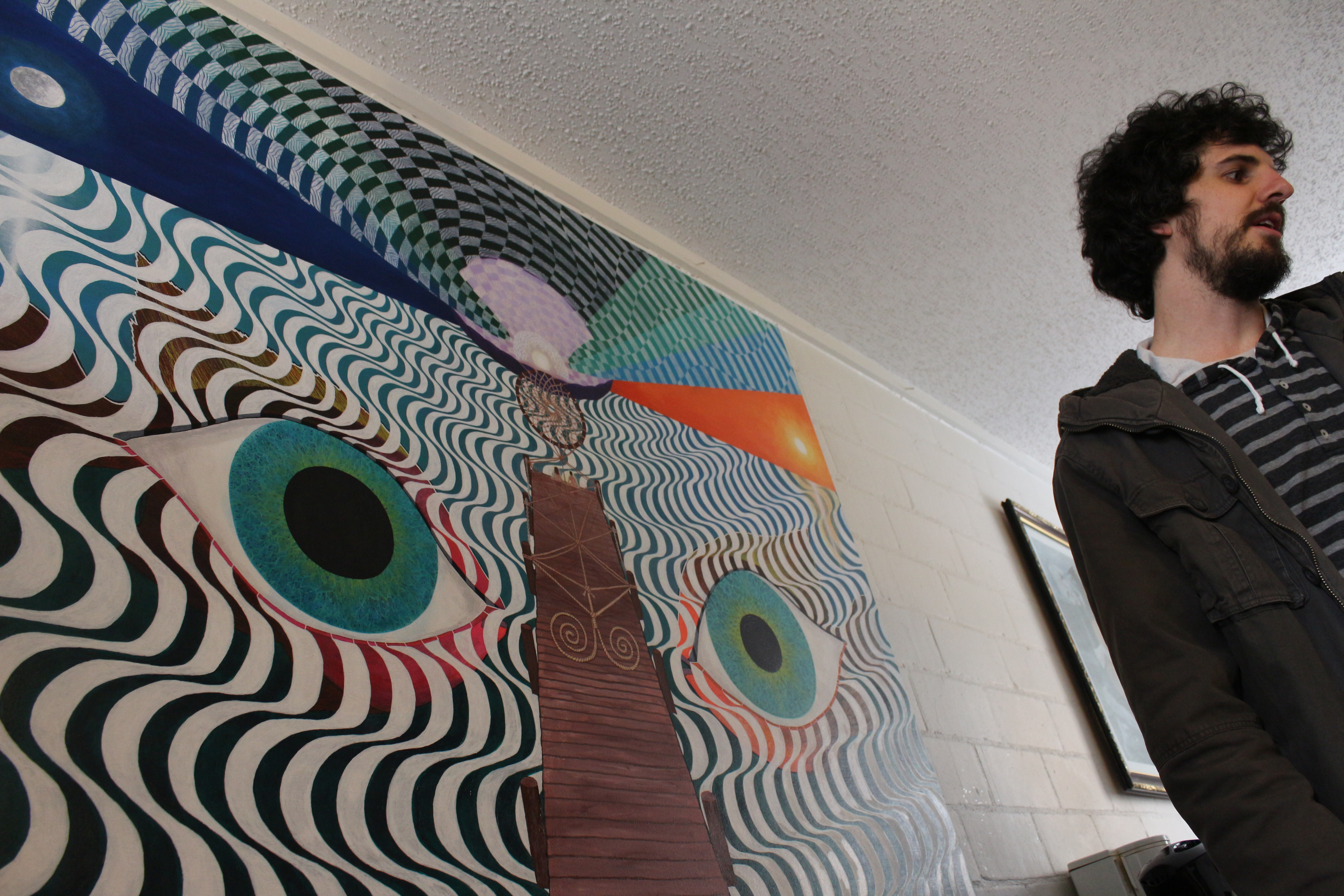 Artist Stephen Ferguson stands in front of his painting that is located in the dining area of Drifter Jack's Hostel. By Joan Vinson