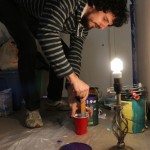 Artist Stephen Ferguson concocts a paint mixture for a mural he is working on at Drifter Jack's Hostel. By Joan Vinson