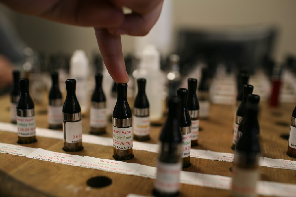 A customer glances over the many e-juice flavors.  Flavor Vapor features over 100 liquid flavors, priced between seven and 16 dollars, and occasionally takes requests for new ones.