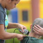 Smile volunteer Dakota Batch shaves Ricky Llamas's head.