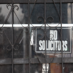 "An old ""No Solicitors"" sign and metal bars protect the bar from burglers and other unwanted guests. Photo by: Tom Hushen"
