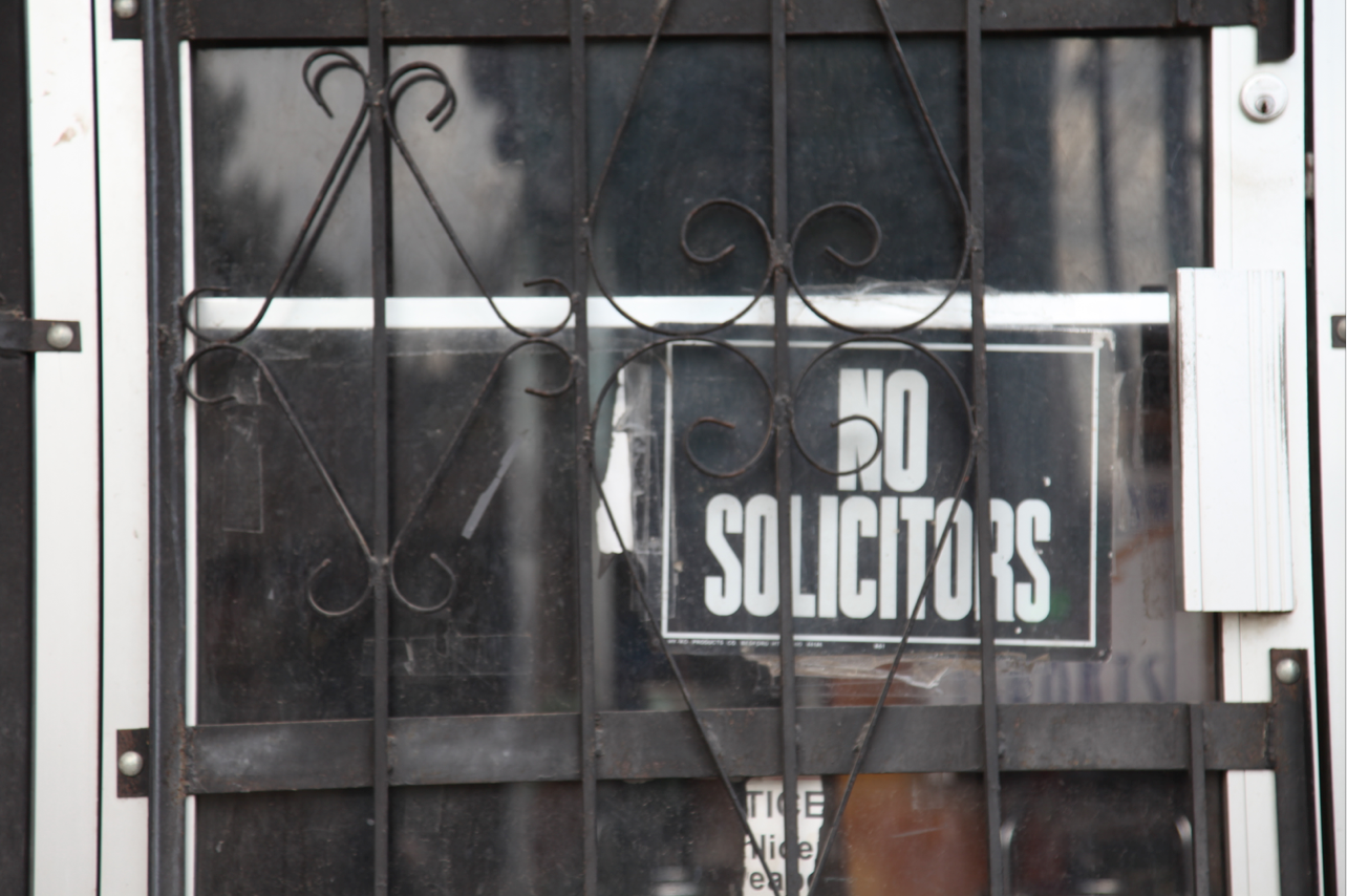 """An old """"No Solicitors"""" sign and metal bars protect the bar from burglers and other unwanted guests. Photo by: Tom Hushen"""