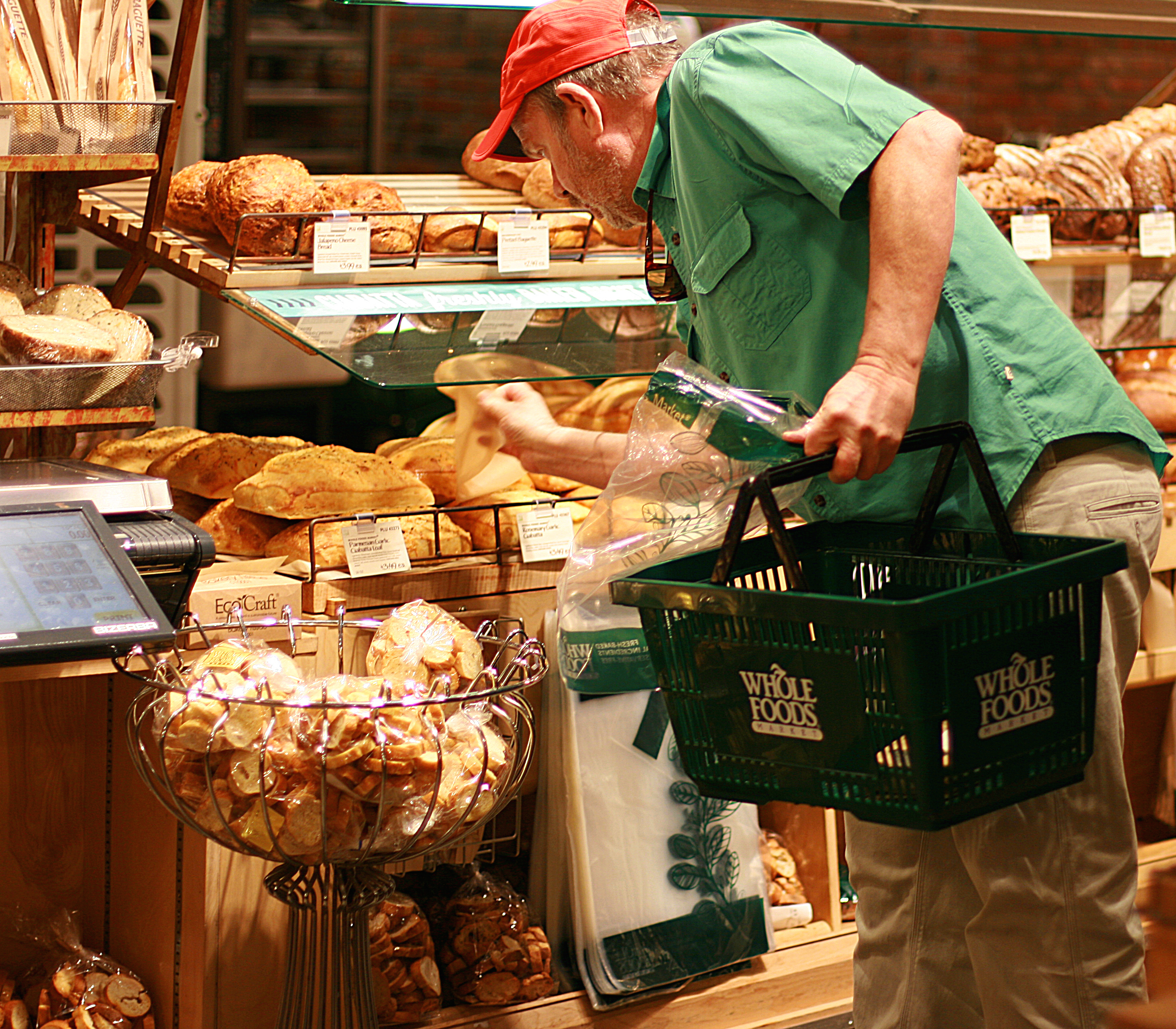 A whole foods shopper inspects prices and food. While services such as Instacart may cut down on actual shopping time, wait times for delivery can take up to two hours and customers are trusting someone else to pick their food. Photo by Silvana Di Ravenna