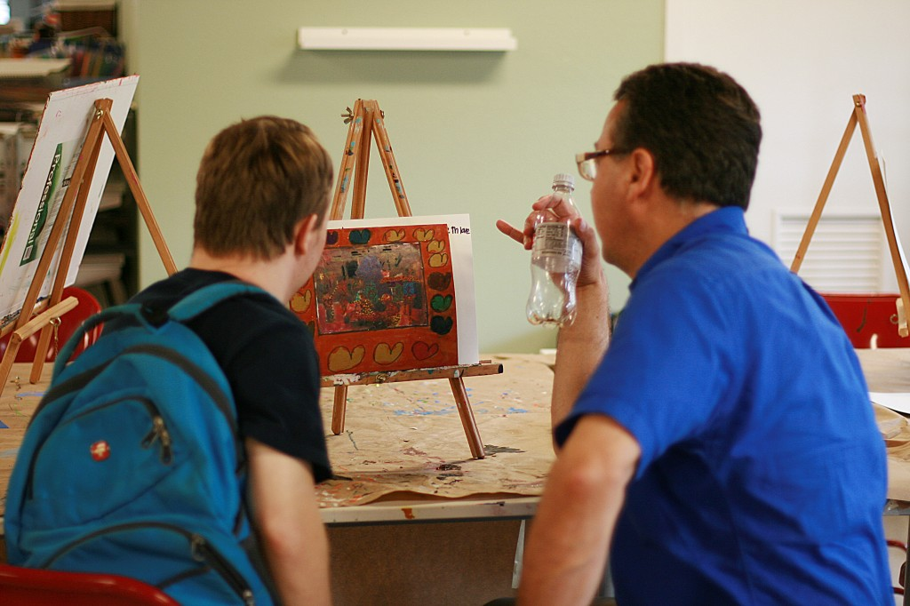 A teacher at the Arc of the Arts studio discusses a painting with artist and student Jared S. Teachers collaborate with the artists to develop create and professional skill sets. (Photo by Silvana Di Ravenna)