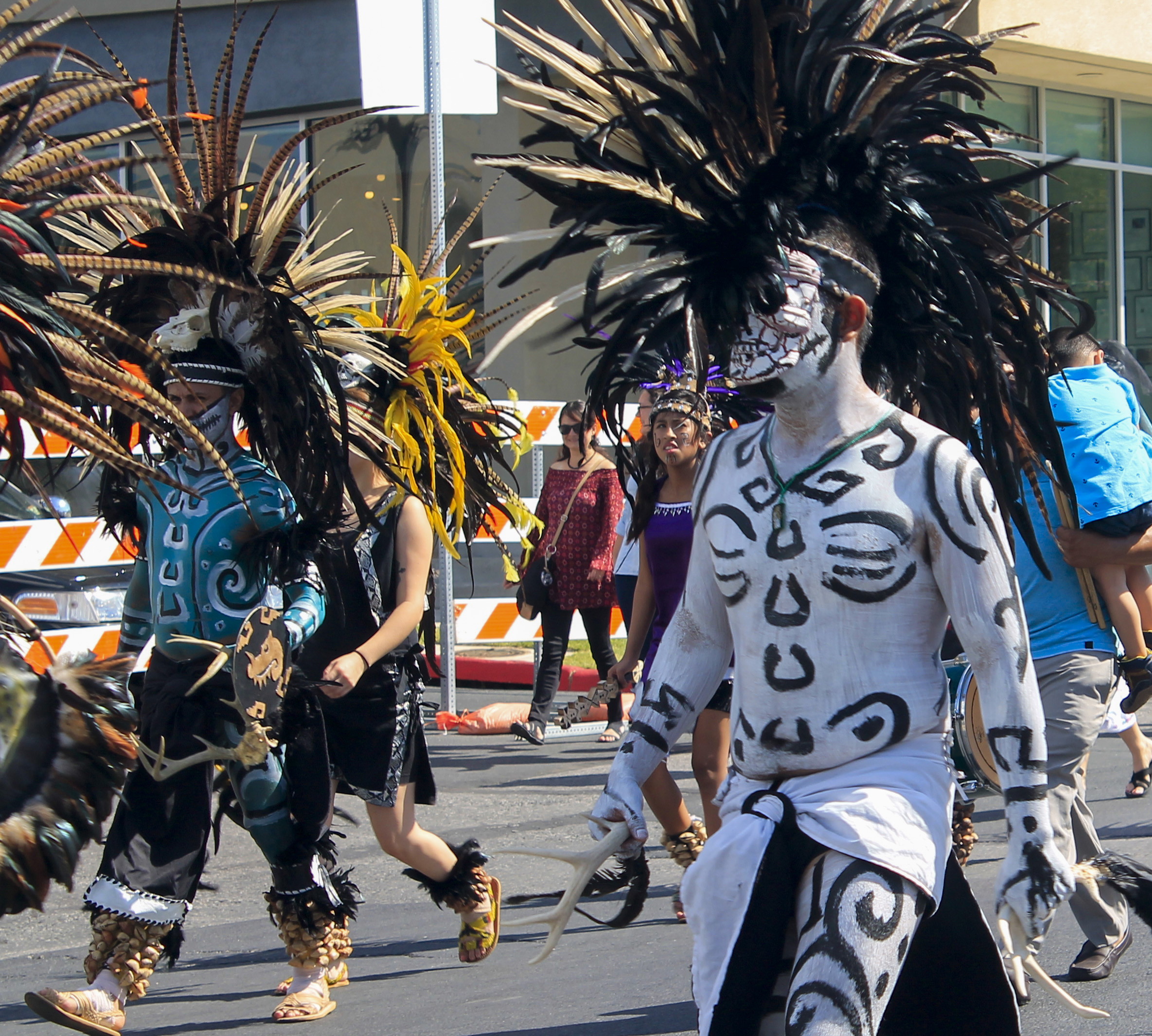 Dancers from Danza Azteca Guadalupana parade through downtown on their way to the Viva la Vida festival's stage. The group has dancers of all ages and sexes and they perform throughout the year. Photo by Alex Vickery. Editing by Olivia Starich.