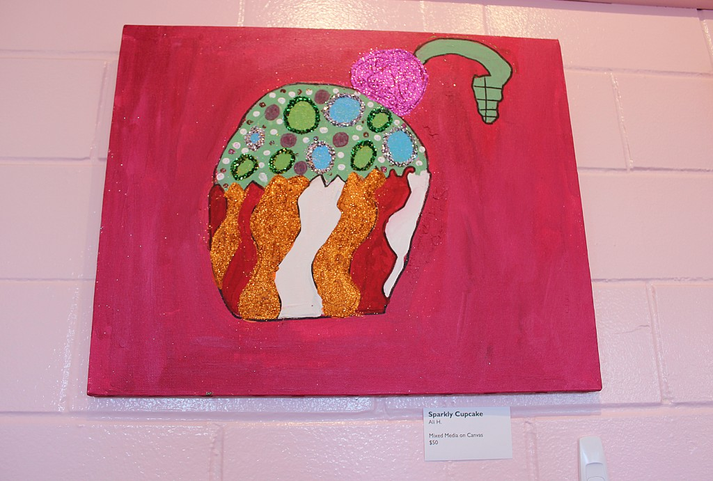 """Sparkly Cupcake"" is one of three Arc of the Arts Studio paintings currently being displayed at Hey Cupcake. Ali H., the artists of the paintings helped set up the display, and makes a 20 percent commission on any of the pieces sold. (Photo by Alice Kozdemba)"