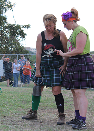 Brittney Boswell (right), the first woman to compete in Highland Games in Texas 11 years ago, offers advice to a fellow athlete before the weight over bar event.