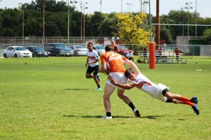 A player from the White team leaps in attempts to tackle a player from the Orange team during the Orange and White scrimmage.