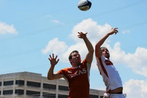 Members of the Texas Rugby team reach to the sky for a pass during the Orange and White scrimmage.