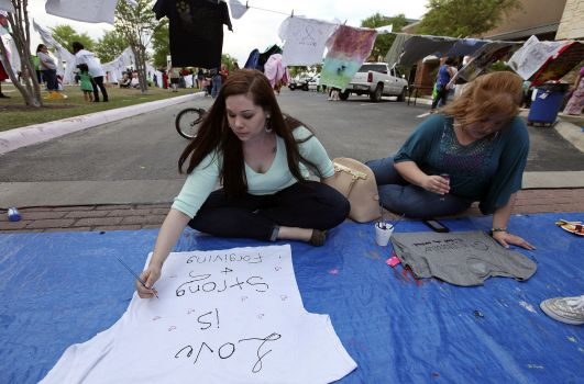 "Elena Ibarra paints sign for Take Back the Night Rally in San Antonio  Texas displaying ""Love is Strong and Forgiving."" [mysanantonio.com]"