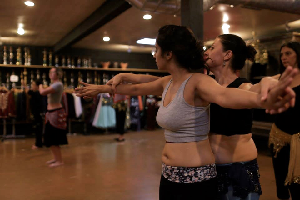 Belly dancing instructor  Zein Al-Jundi adjusts one of her students in class. She bounces from person to person and physically tweaks her students to help their form.