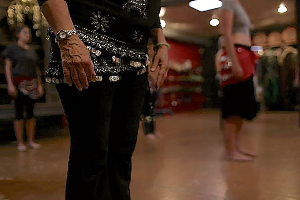 A student dons a hip scarf for Al-Jundi's belly dancing class. Hip scarves a part of less conservative belly dancing attire and are used to help dancers feel their hip movements better.
