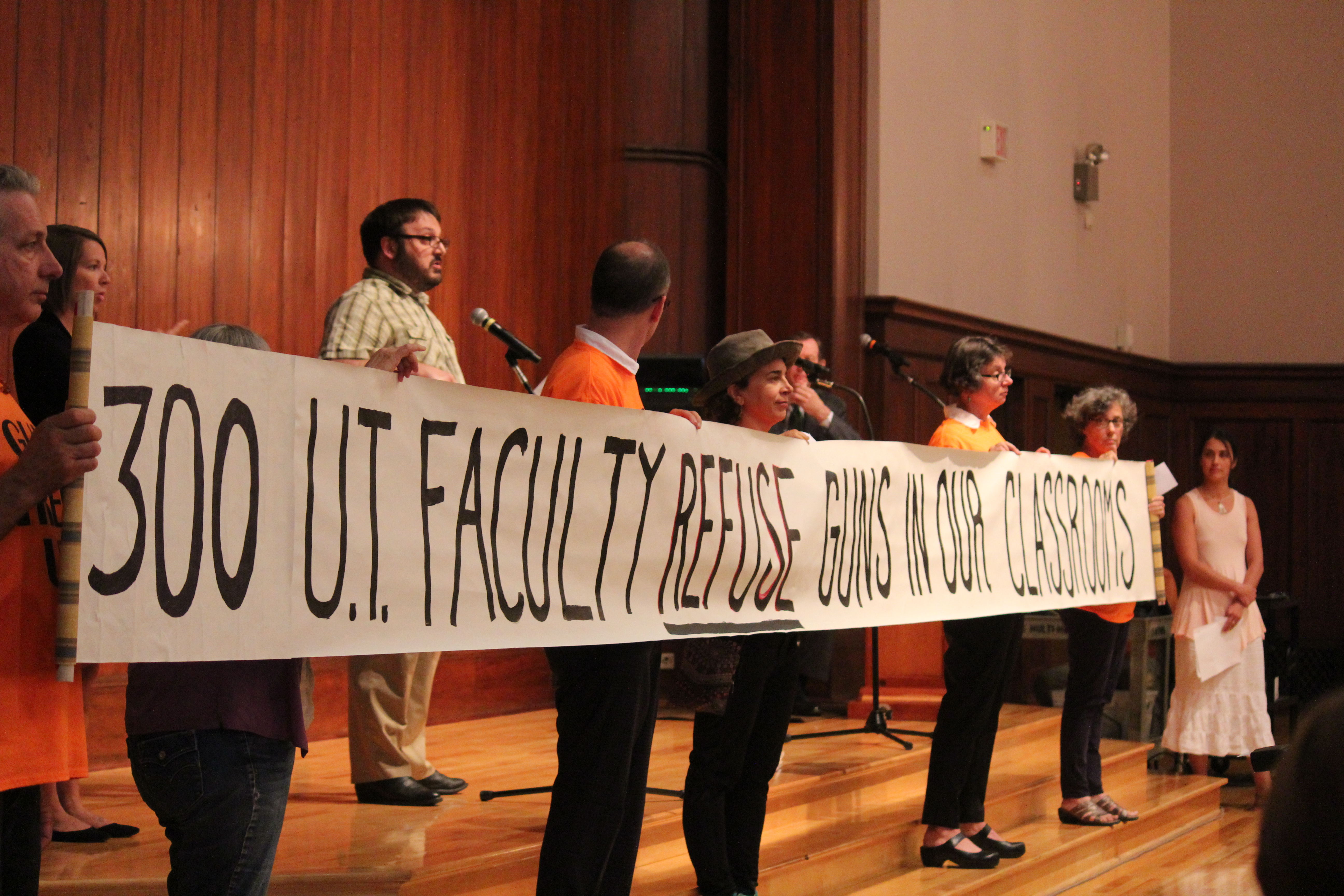 "At the Oct. 5 open carry forum, members of Gun Free UT display a banner that states: ""300 UT Faculty Refuse Guns In Our Classrooms."""