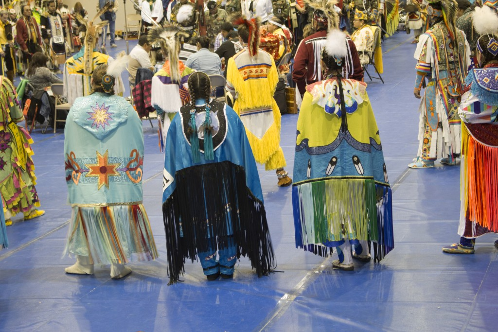 People gathered around the gym, dressed in Native American attire to participate in events during the Pow Wow.