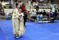 Woman in traditional Native American attire looks on to the men performing.