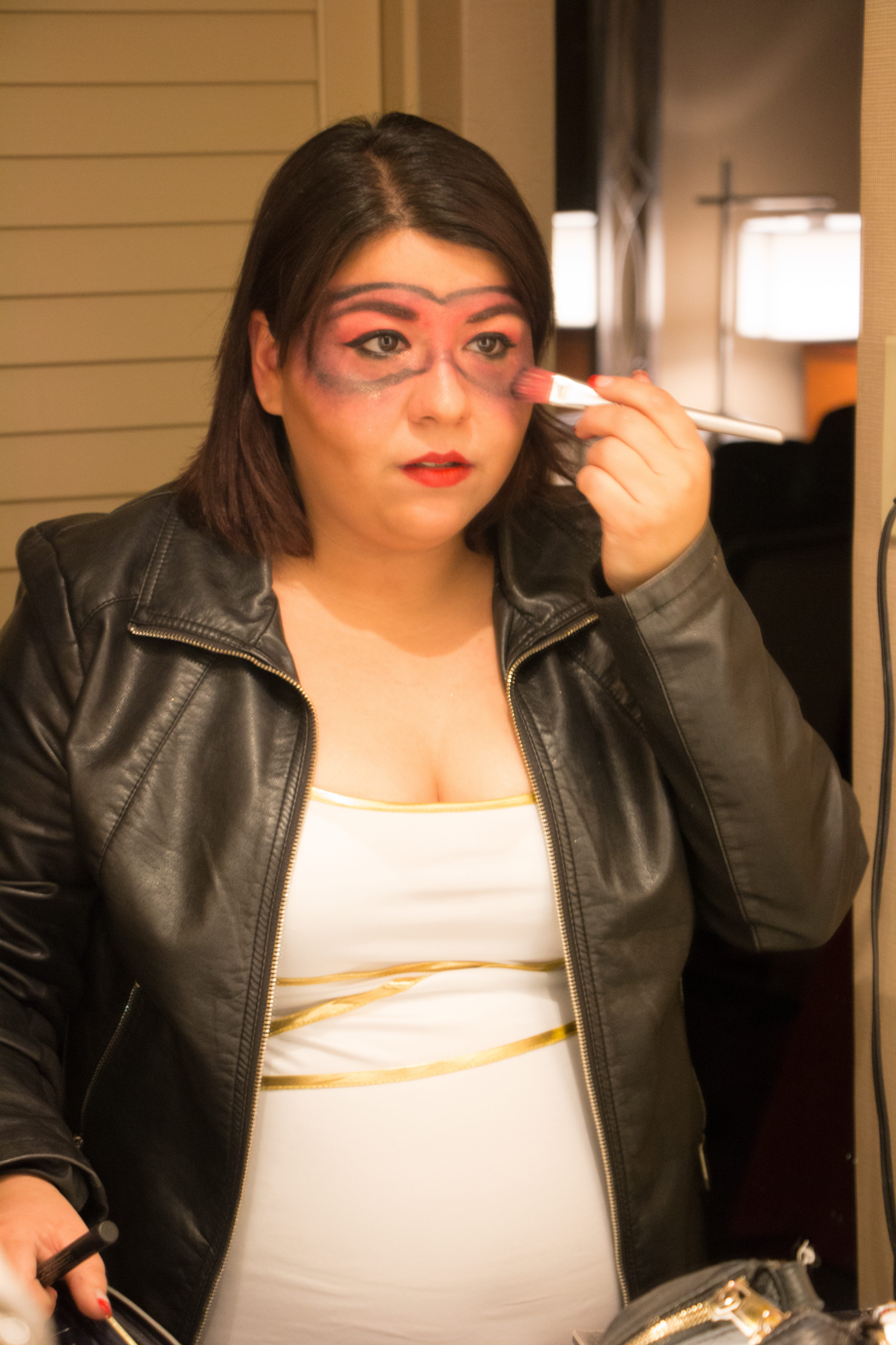 Iliana Arizpe gets her Cupid costume ready by applying extra makeup.