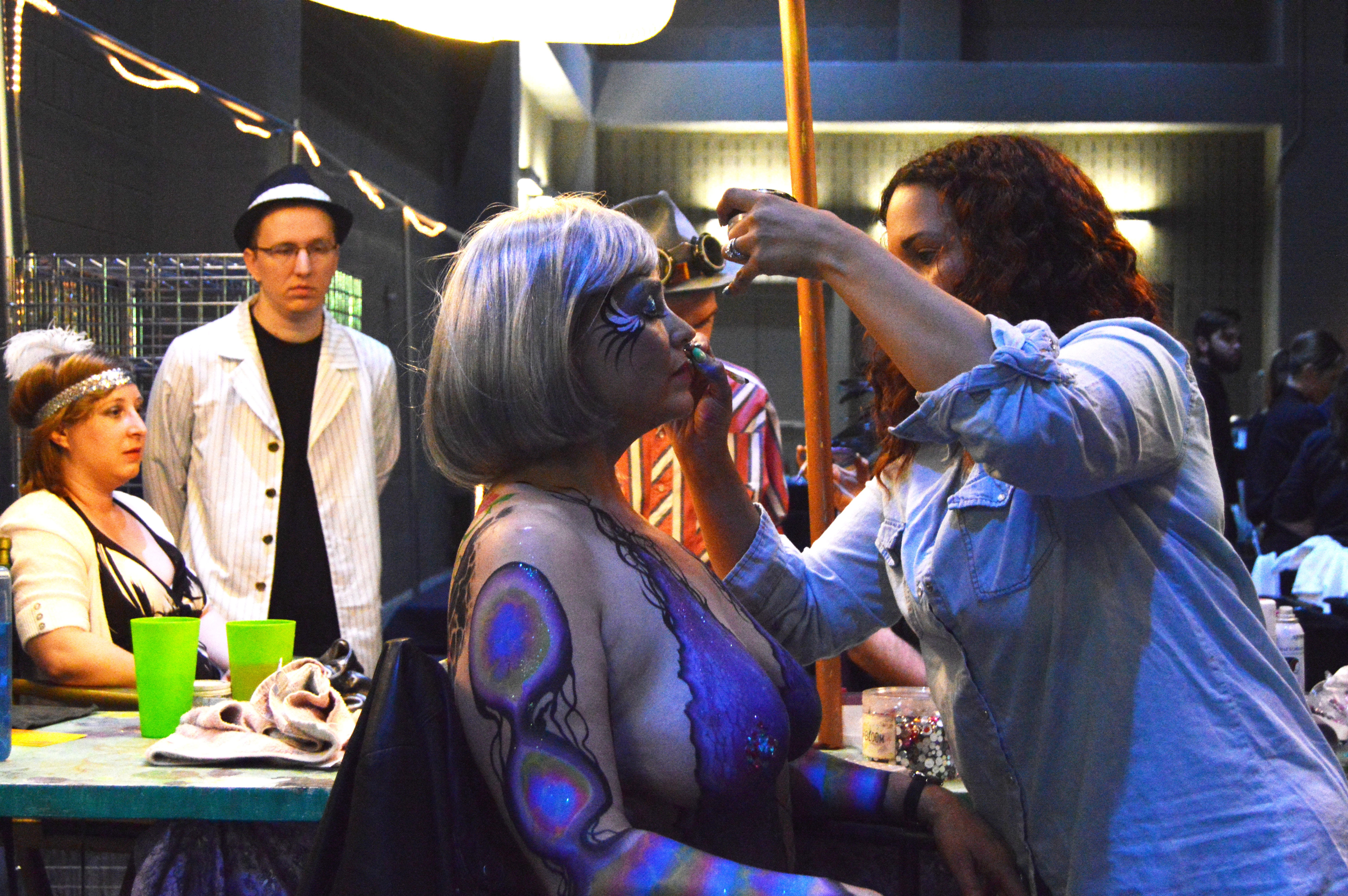 Carnaval's body painter, known as Kiwi, has a line at her booth throughout the entire evening. Women and men arrive topless to get painted with her intricate designs.