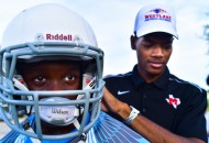 Reagan Football Academy coach Kelton Malone fits a new helmet on player Micah Thomas. Malone heads the program, designed to train players before they come to Reagan High School.