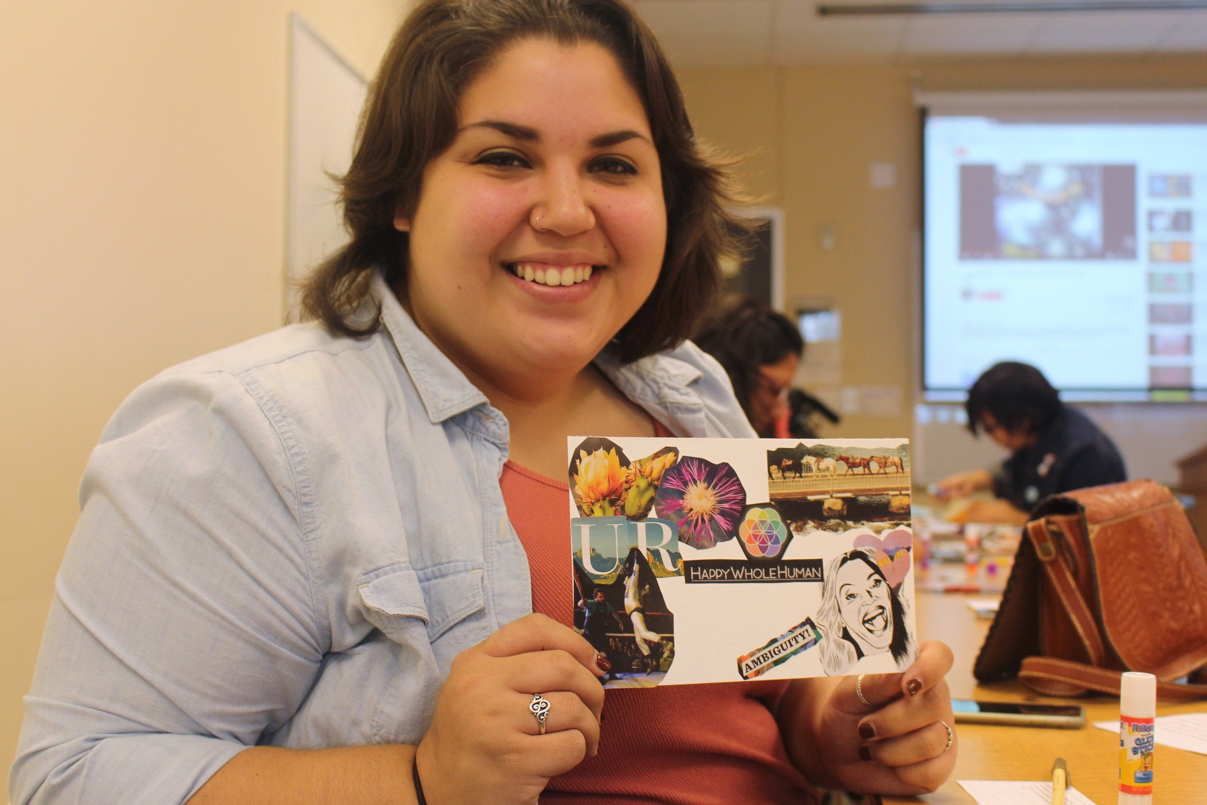 Raven Rojas holds her semi-finished collage at the Self-Healing Through Artistic Affirmations workshop.